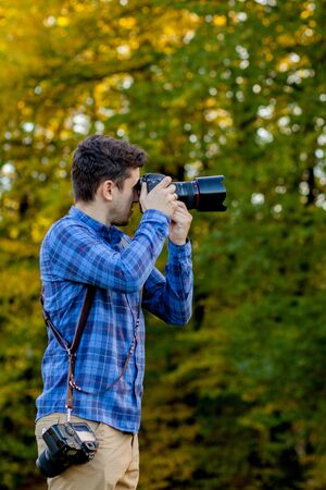 Professional photographer in action with two cameras on a shoulder straps. Stock Photo