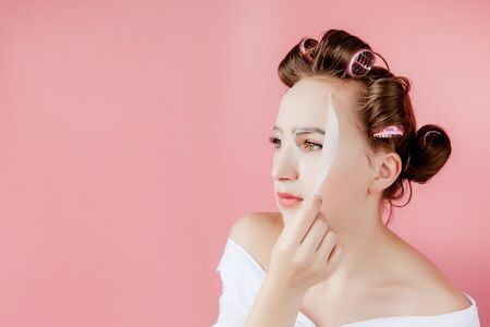 Beautiful young girl with a mask and curlers touching her face