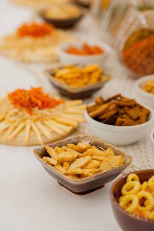 A lots of salty snacks on a table, many cheese and crackers on the table with snacks. Reklamní fotografie