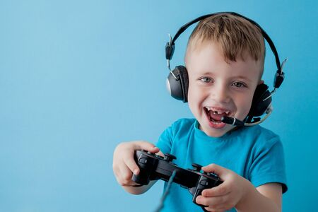 Little kid boy 2-3 years old wearing blue clothes hold in hand joystick for gameson blue background children studio portrait. People childhood lifestyle concept. Mock up copy space. Stockfoto