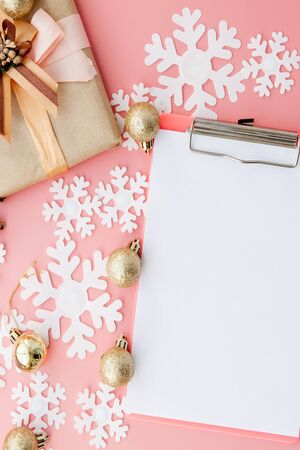Christmas gifts, Christmas ornaments and an open blank notebook on pink background. Flat lay. Top view