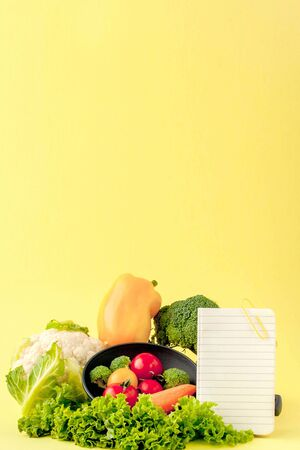 Vegetables and notebook with copy space on yellow background. Bio Healthy food, Organic vegetables on yellow background. Stock Photo - 133350824