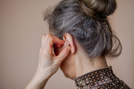 closeup senior woman inserting hearing aid in her ears. Foto de archivo