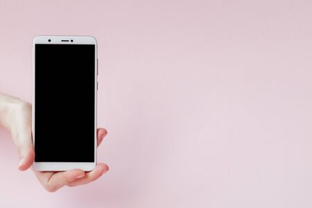 Modern mobile phone in a womans hand on pink background.