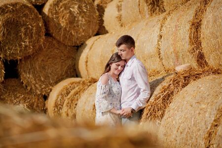 Happy young couple on straw, romantic people concept, beautiful landscape, summer season.