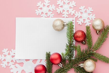 New year concept. Goals list in notepad, gift box and christmas decoration on pink pastel color with copy space.