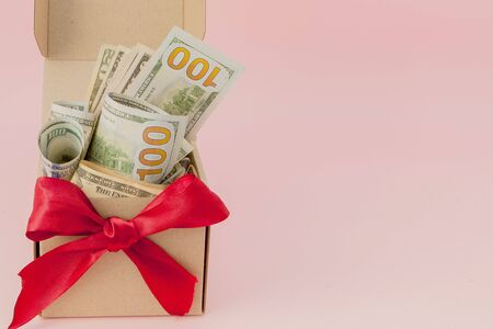 Gift box with dollars on pink background close up.
