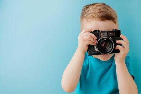 Petit garçon avec un vieil appareil photo sur fond bleu. Banque d'images