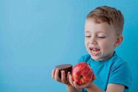 Portrait happy, smiling boy choosing junk food. Healthy versus unhealthy food. Healthy vs unhealthy eating, teenager choosing between cookie or an apple. Stock Photo