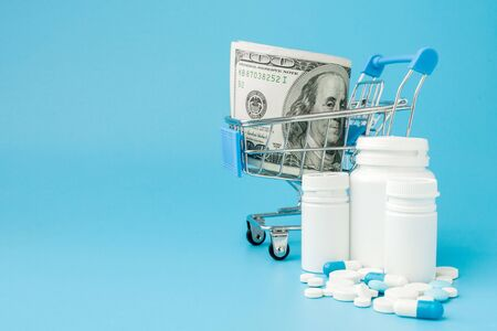 Scattered pharmaceutical medicine pills, tablets and capsules on dollar money isolated on blue background. Medicine expenses