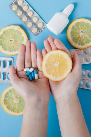 Medications, pills, thermometer, traditional medicine for treating colds, flu, heat on a blue background. Maintenance of immunity. Seasonal diseases. Top view. Medicine flat lay.