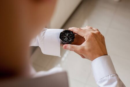 The groom looks at his watch to check the time. The watch is worn on the mans hand. Grooms morning preparation before wedding. 스톡 콘텐츠