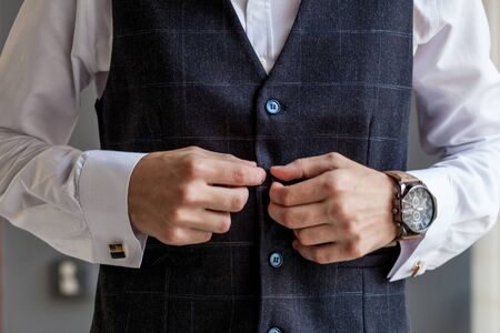 Man gets ready for work by buttoning up his business shirt. Grooms morning preparation before wedding. 스톡 콘텐츠