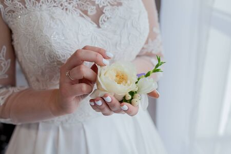 Close-up of the brides hands holds a boutonniere. boutonniere with red rose. 스톡 콘텐츠