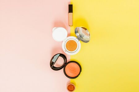 Make up products spilling on to a bright yellow and pink background with copy space, minimal style 스톡 콘텐츠