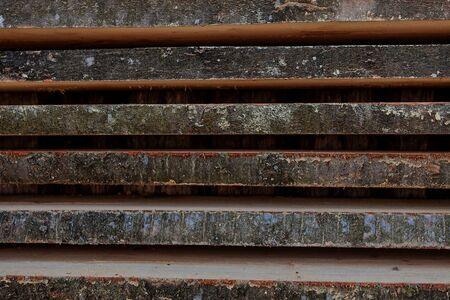 Folded wooden brown and gray planks in a sawmill. Piled alder boards as texture.