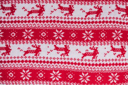 Real red knitted background with white Christmas deer and snowflakes. 스톡 콘텐츠