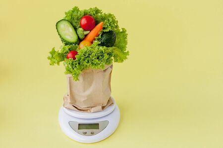Fresh vegetables on scales on yellow background. Vegan and healthy concept