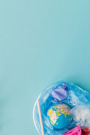 The concept of reducing plastic bags use: Modeled globes are sunk in many white plastic bags. Meaning, plastic bags are about to overflow the world.