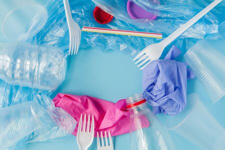 Top view of various kinds of disposable plastic waste on blue background, copy space.