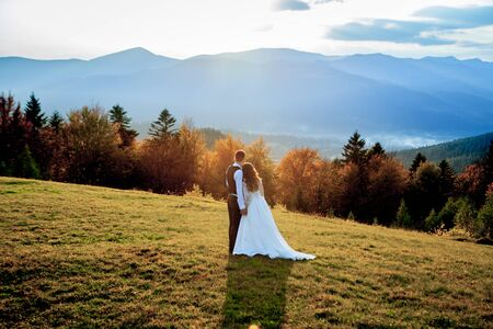 Beautiful wedding couple, bride and groom, in love on the background of mountains. The groom in a beautiful suit and the bride in a white luxury dress. Wedding couple is walking.