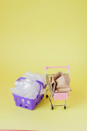 polythene and paper bags in a shopping basket on a yellow background.