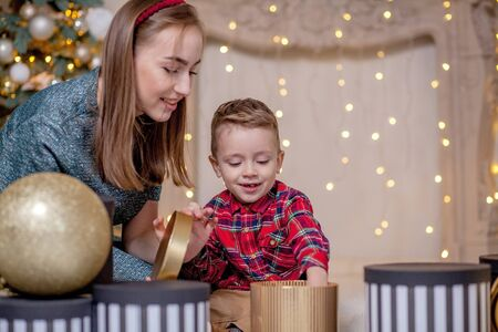 Mother gives Christmas gift to his little son for a New Year. Mom and son opening Christmas presents