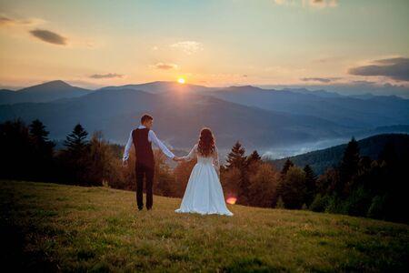 Braut und Bräutigam beobachten den Sonnenuntergang auf dem Hügel Standard-Bild