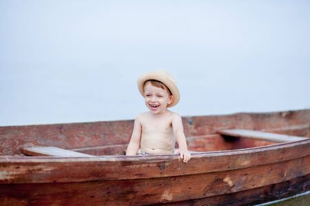 Little boy is resting in a boat on the lake.