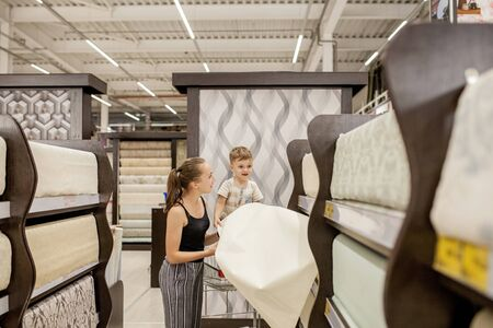 shopping time: beautiful young woman with her son having fun in the DIY supermarket department store choosing for buying wallpaper holding looking at design image.