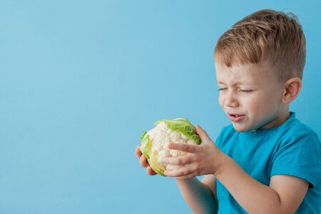 Little Boy Holding Broccoli in his hands on blue background, diet and exercise for good health concept.