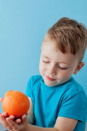 Little Boy Holding an Orange in his hands on blue background, diet and exercise for good health concept.