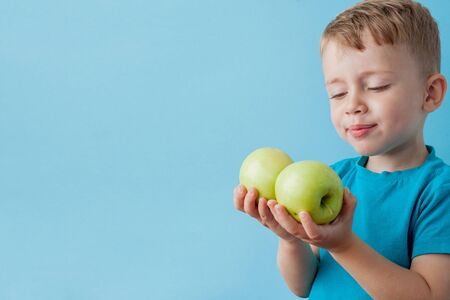 Little Boy Holding an Apples in his hands on blue background, diet and exercise for good health concept.