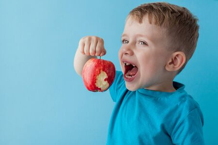 Baby child holding and eating red apple on blue background, food, diet and healthy eating concept.