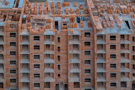 Close-up on a multi-storey residential building under construction from red brick with a part of a crane. The walls of the house in the process of work and architecture.