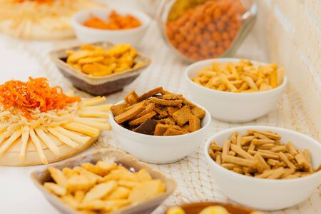 A lots of salty snacks on a table, many cheese and crackers on the table with snacks. 写真素材