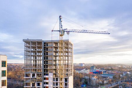 Photo of a multi-storey building under construction. Construction of a residential skyscraper. Background image of the process of building a house with cranes. A high-rise building under construction Zdjęcie Seryjne