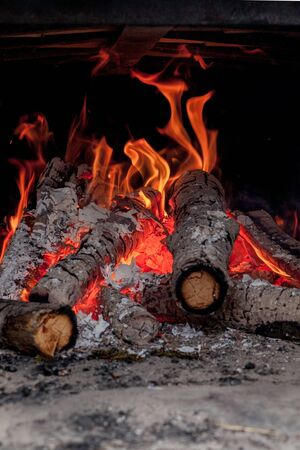 Hot vivid burning birch logs in fireplace on a cold winter day.