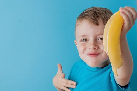 Little Boy Holding and eating an Banana on blue background, food, diet and healthy eating concept Zdjęcie Seryjne