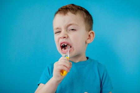 Little cute boy brushing his teeth on blue background