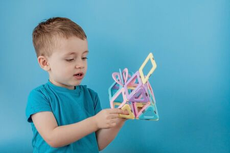 Boy looks through the shape in the color constructor with the connection of the magnets.