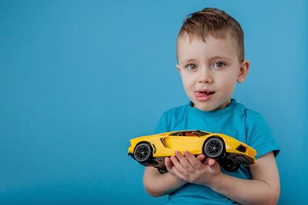 Little boy playing with a big yellow car on blue background.