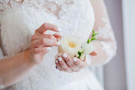 Nahaufnahme der Hände der Braut hält eine Ansteckblume. Ansteckblume mit roter Rose.