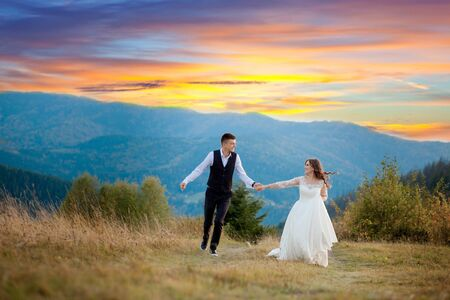 Happy gorgeous bride and stylish groom run and having fun, wedding couple, luxury ceremony at mountains with amazing view. Zdjęcie Seryjne