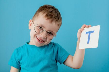 Cute little boy with letter on blue background. Child learning a letters. Alphabet. Zdjęcie Seryjne