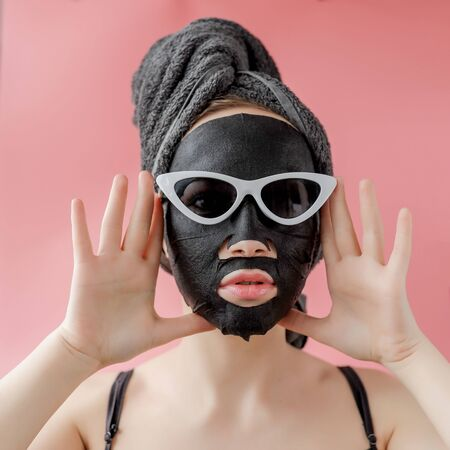Young woman in glasses appling black cosmetic fabric facial mask on pink background. Face peeling mask with charcoal, spa beauty treatment, skincare, cosmetology. Close up. Stock Photo