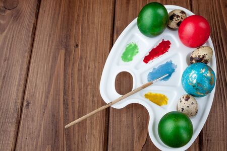 Colored eggs and paint on a wooden table, Easter background. Reklamní fotografie