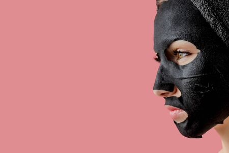 Young woman apply black cosmetic fabric facial mask on pink background. Face peeling mask with charcoal, spa beauty treatment, skincare, cosmetology. Close up.