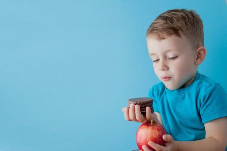 Portrait happy, smiling boy choosing junk food. Healthy versus unhealthy food. Healthy vs unhealthy eating, teenager choosing between cookie or an apple.