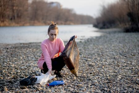 Young female volunteer collecting garbage on the river.